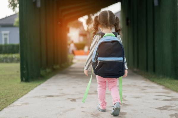 Young girl walking with a backpack